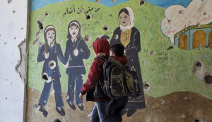 "Children walk beside a painted wall inside Jarmaq school in Yarmouk camp April 14, 2015. The text on the wall reads in Arabic ""It's my right to learn."" Picture taken April 14, 2015. REUTERS/Moayad Zaghmout - RTR4XFMX"