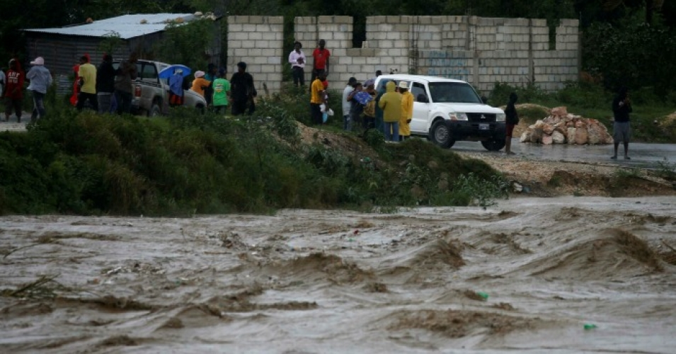 People watch as river waters roll through Port-au-Prince on Oct. 4. (Photo: Carlos Garcia Rawlins/Reuters)